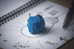 drawing of a light bulb with a wadded up blue paper shows product launch ideas through to you by public relations company 10 to 1 pr
