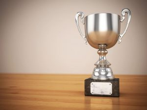 a silver trophy on a wooden table represents award submissions for your company's public relations