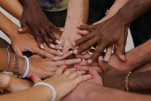 men and women of many races with thier hands together shows public involvement and how a public relations company like 10 to 1 pr can improve public image