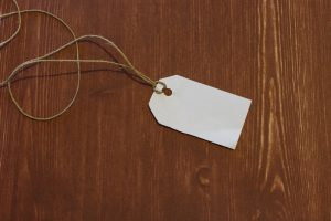 white label against a brown wooden background with brown thread